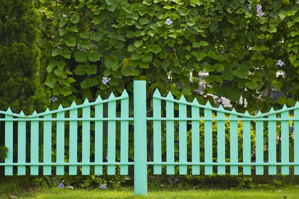 Забор с вертикальными элементами разной высоты.