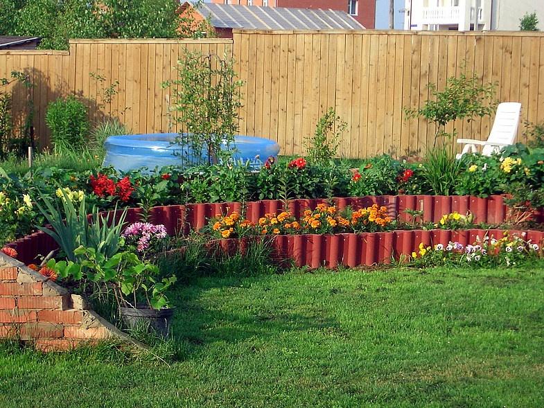 Грядки под овощи и цветы в зоне отдыха на даче