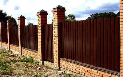Забор из профнастила, закреплённый на кирпичной основе